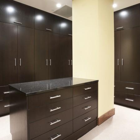 Modern master bedroom closet with dark stain.